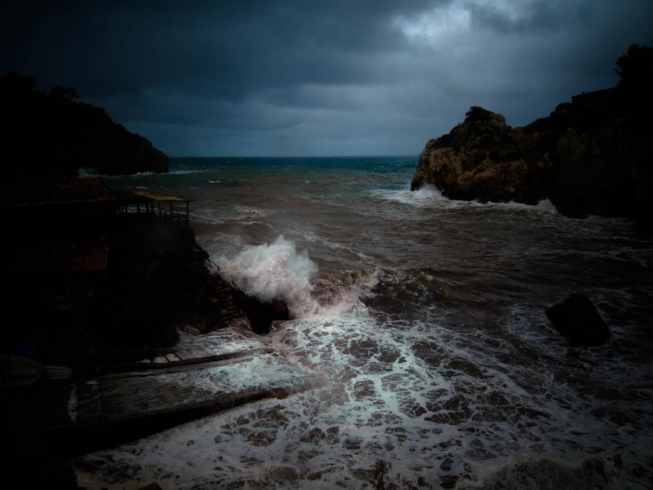 Waves breaking against Cas Patro March retaurant.